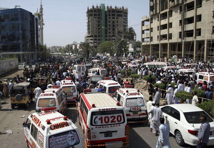 Numerosas personas acuden al lugar donde a explosionado una bomba a la entrada de una mezquita tras las el rezo musulmán del viernes, en Karachi, Pakistán. (EFE)
