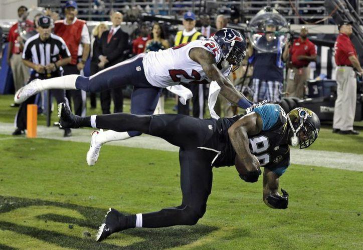 El ala cerrada de Jacksonville, Marcedes Lewis (89) durante la anotación de un touchdown frente al esquinero de los Texans, Kareem Jackson (25). (Agencias)