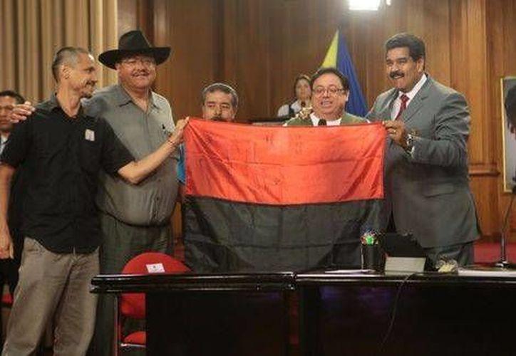 De izquierda a derecha, el nieto de Allende, Francisco Villa, Emiliano Zapata y Sandino entregan a Maduro simbólicamente la bandera de unión revolucionaria. (Milenio)