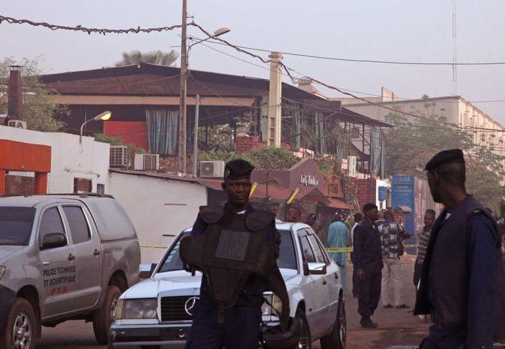 Un club nocturno (atrás) popular entre los expatriados en la capital de Mali es rodeado por fuerzas de seguridad luego de haber sido atacado. (Agencias)