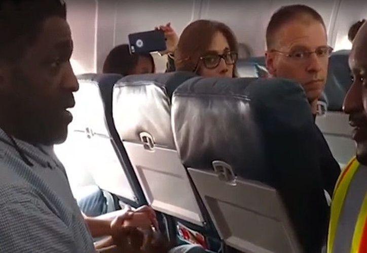 Un grupo de pasajeros grabó el momento en el que la tripulación de Delta Airlines le pedía a un hombre que se bajara del avión. (Impresión de pantalla)