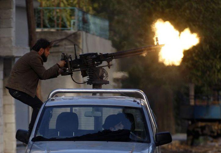 Un rebelde sirio dispara  durante un enfrentamiento con  fuerzas del ejército en  Harem, en las afueras de Idlib, Siria. (Agencias)