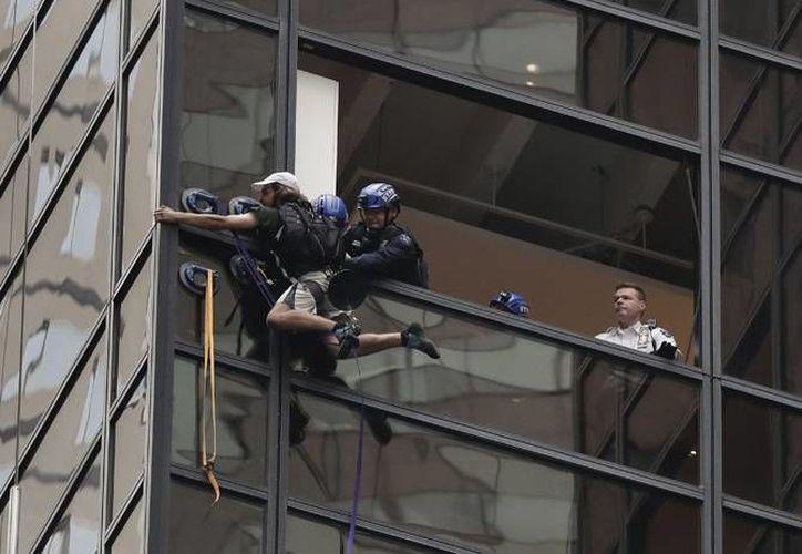 Un hombre trató de subir a la cima de la Torre Trump en Nueva York utilizando unas ventosas, pero luego de una hora de escalada, fue detenido por agentes de seguridad, que lo interceptaron desde una ventana. (Foto AP/Julie Jacobson)