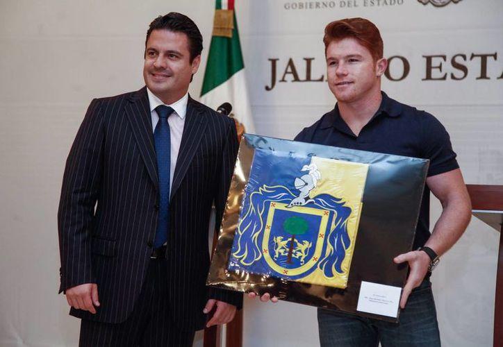 El gobernador de Jalisco, Aristóteles Sandoval, entregó al Canelo Álvarez la bandera con el escudo de la entidad. (jalisco.gob.mx)