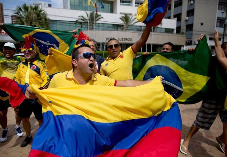 Gobierno de Colombia dio tarde libre a los burócratas para que vean el partido de los cafeteros contra Brasil. En la imagen, aficionados de ese país animan a la Selección, a las puertas del hotel donde el equipo se hospeda, en Fortaleza. (AP)