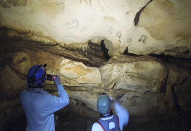 """Grabados rupestres figuras de dioses y geométricos, parte de los tesoros de las grutas de Yucatán. En la imagen, los especialistas explican el significado de las """"pinturas"""" mayas. (Milenio Novedes)"""