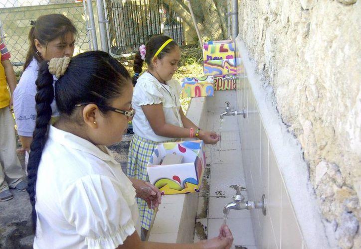 Las autoridades recomiendan seguir las medidas de higiene, como el lavado frecuente de manos. Imagen de un par de niñas mientras se jabonan en una pileta de su escuela. (Milenio Novedades)