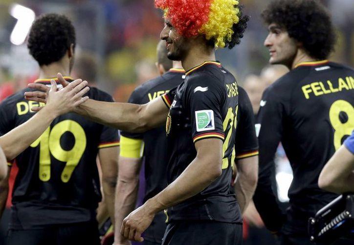 Jugadores de Bélgica celebran su clasificación a octavos con marcha perfecta de tres partidos ganados, aunque todos por diferencia de un gol. (Fotos: AP)