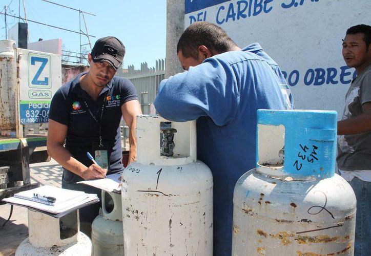 La báscula de repeso fue instalada sobre la prolongación de la avenida Alvaro Obregón, y las tres unidades de reparto fueron detenidas para la supervisión, cilindro por cilindro. (Ernesto Neveu/SIPSE)