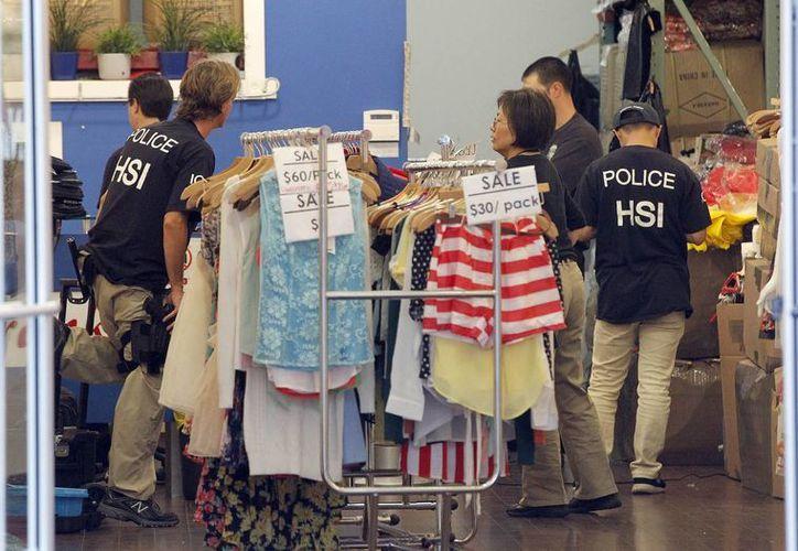 Agentes policiacos revisan una tienda de ropa durante un operativo en Los Angeles. (Foto: AP)