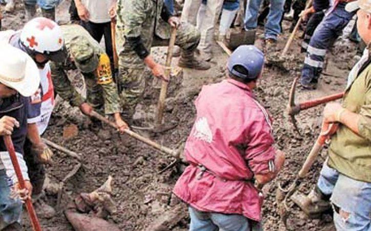 Rescate de uno de los cuerpos sepultados por el deslave de un cerro de arena, en Veracruz. (Milenio)