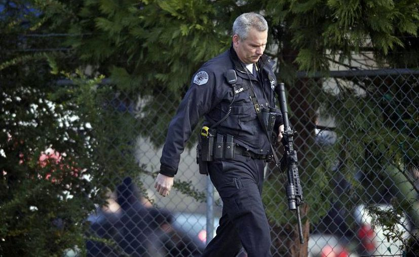 Un policía inspecciona el área donde ocurrió el tiroteo, en Vancuover, Washington, EU. Dos personas murieron. (Agencias)