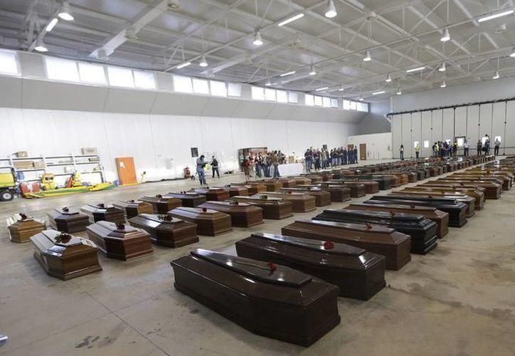Cadáveres de los migrantes que fallecieron en el naufragio fueron alineados en el aeropuerto de Lampedusa. (Agencias)