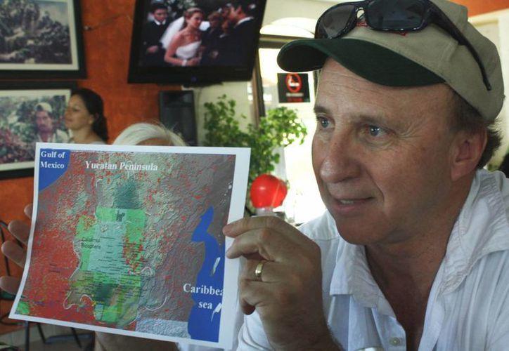 El arqueólogo Richard D. Hansen muestra en un mapa el peligro que corre la reserva de Calakmul. (Alida Martínez/SIPSE)