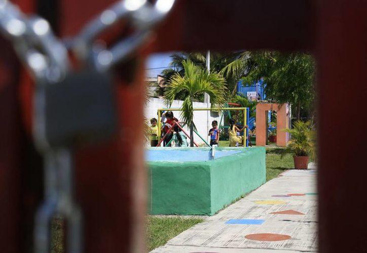 Algunas escuelas permiten el acceso de los alumnos por la reja de servicio; la puerta principal tiene cadena y candado. (Harold Alcocer/SIPSE)