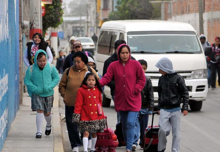 Durante la temporada invernal, el Sistema Nacional de Protección Civil recomienda prestar especial atención a los niños, personas mayores, enfermos y personas en situación de calle. Imagen de niños yendo a la escuela, en la Ciudad de México. (Archivo/Notimex)