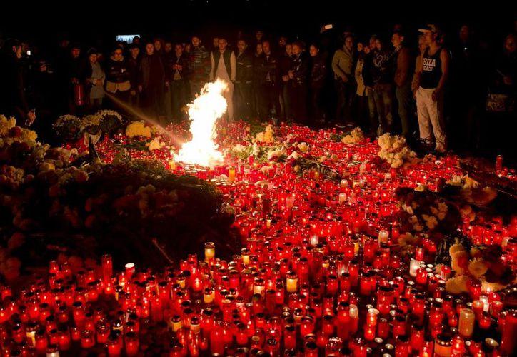 Rumanos se reúnen en torno a una ofrenda con velas en recuerdo de las víctimas de un terrible incendio en un centro nocturno, que dejó 27 muertos. (AP)