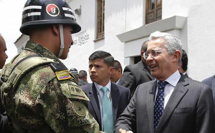 El ex presidente colombiano Álvaro Uribe saluda a un soldado camino a su encuentro con el mandatario Juan Manuel Santos en el palacio presidencial en Bogotá, Colombia, el miércoles 4 de octubre de 2016. (AP Foto/Fernando Vergara)