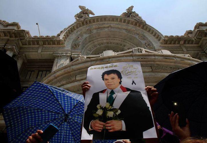 Los restos de Juan Gabriel serán depositados en la casa que fuera de su madre, en Ciudad Juárez. En la imagen, fans del cantautor sostienen una fotografía, durante una concentración frente al Palacio de Bellas Artes, en la Ciudad de México. (Notimex)