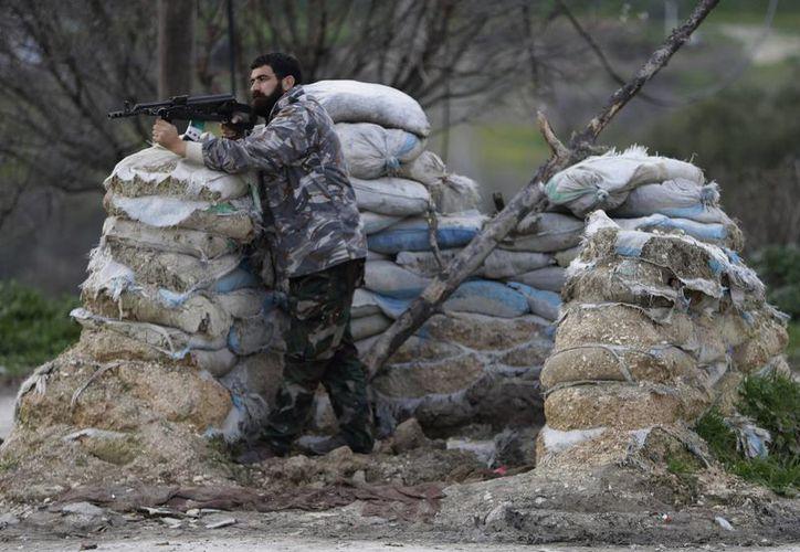 Un rebelde sirio toma posición en la entrada de la villa de Yacoubieh, en el noreste del país. (Agencias)