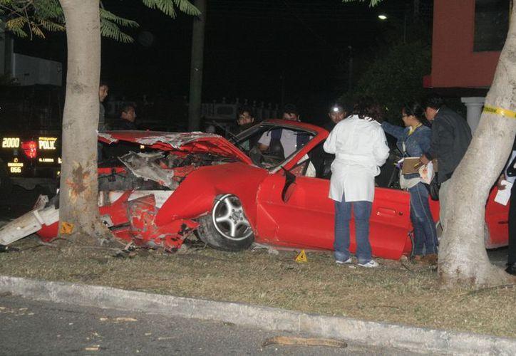 El Mustang convertible quedó destrozado al impactar contra un árbol en la avenida Jacinto Canek. (Jorge Sosa/SIPSE)