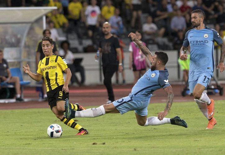 El futbolista del Borussia Dortmund Emre Mor (izq) se enfrenta a Nicolás Otamendi (c), del Manchester City, durante su partido de la International Champions Cup en el Centro Shenzhen Universiade de Shenzhen, en China. (EFE)