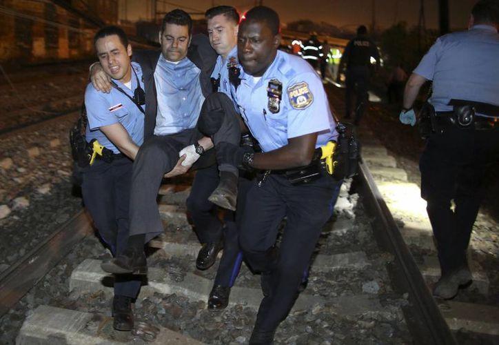 Un pasajero es auxiliado después de que se descarriló un tren de Amtrak cerca de Filadelfia, ayer por la noche. (AP Foto/Paul Cheung)