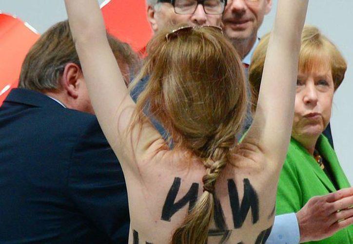 Una manifestante en topless con un mensaje escrito en su espalda camina hacia Vladimir Putin y la canciller alemana, Angela Merkel. (Agencias)