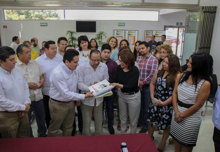 El presidente estatal del PRI, Carlos Pavón Flores, entrega a la presidenta del Iepac, María de Lourdes Rosas Moya, la plataforma electoral 2015-2018. (SIPSE)