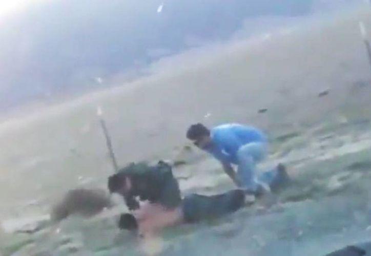 En el video se observa cómo un agente de la Patrulla Fronteriza golpea a un indocumentado, a pesar de que ya estaba sometido y acostado en el piso, mientras es ayudado por un hombre vestido de civil. (Captura de pantalla)