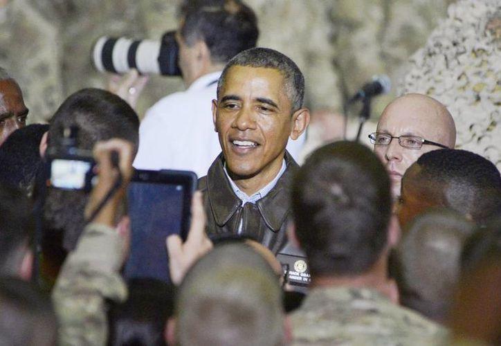 Fotografía facilitada por el Departamento de Defensa de E.U., que muestra al presidente del país, Barack Obama (c), mientras saludó ayer a soldados de la base aérea de Bagram, Afganistán. (EFE)