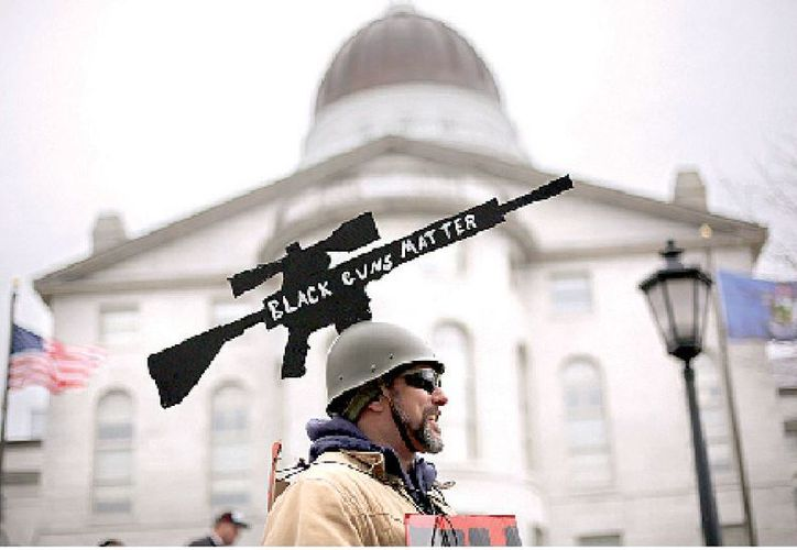 Joe Dobbins of Hartford, Maine, wears a cut-out of an AR-10 tactical rifle while attending a gun rights rally, Saturday, April 14, 2018, at the State House in Augusta, Maine. Gun rights supporters rallied across the United States to counter a recent wave of student-led protests against gun violence.