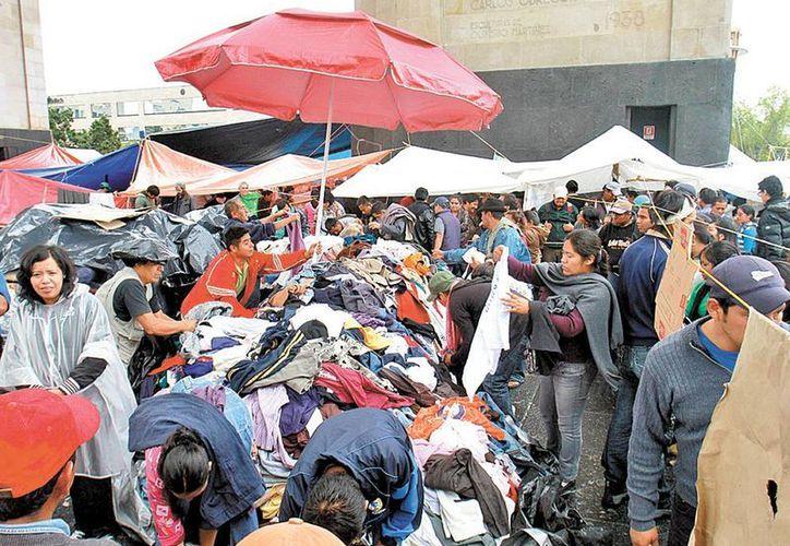 Profesores en el Monumento a la Revolución escogen la ropa que les ha sido donada. (Milenio Novedades)