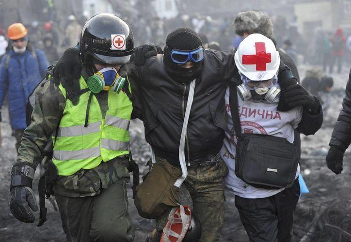 Unos médicos ayudan a un manifestante herido durante una protesta antigubernamental en Kiev, el pasado 23 de enero. (EFE/Archivo)