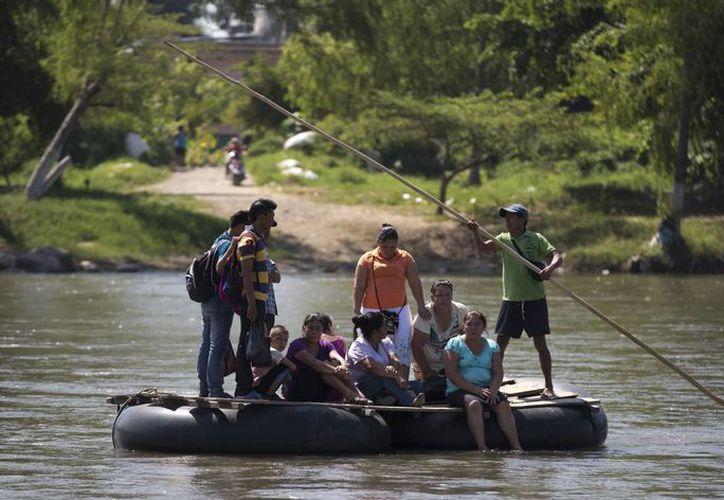 Varios inmigrantes centroamericanos tratan de cruzar en una balsa improvisada el río Suchiate, límite de México y Guatemala. (Agencias)