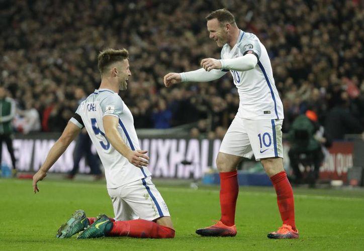 Los ingleses dominaron todo el encuentro y con sendos remates de cabeza, golearon 3-0 a los escoceses. En la foto, Cahill celebra con Rooney.(Matt Dunham/AP)
