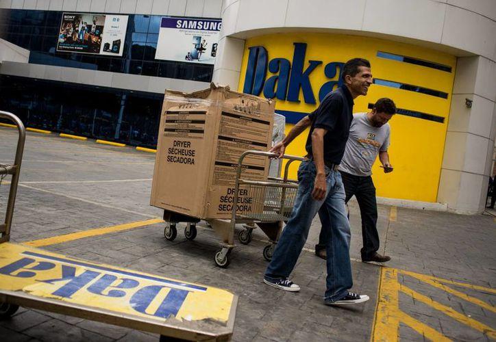 Venezolanos salen tras comprar electrodomésticos en una de las sedes de la cadena de tiendas Daka, en Caracas. (EFE)