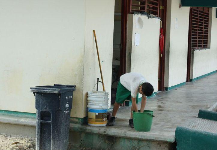 Los estudiantes salen del baño y se lavan las manos en una cubeta. (Alida Martínez/SIPSE)