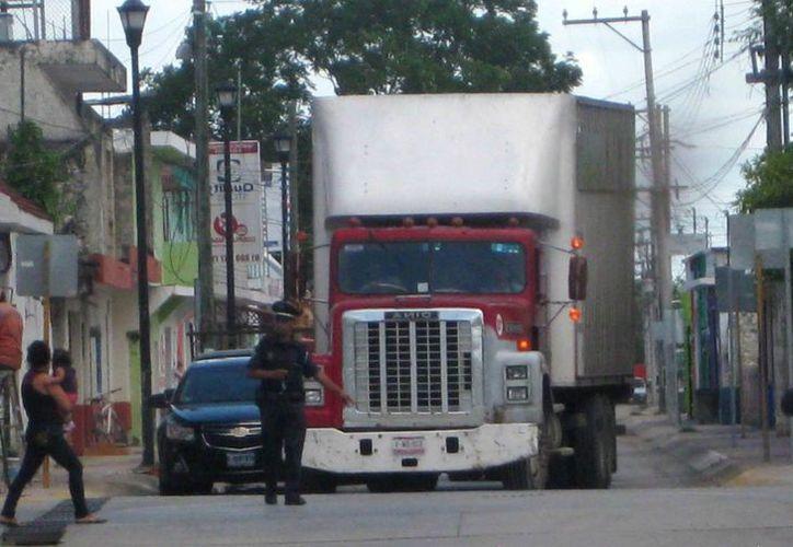 Los enormes vehículos pesados que ocupan esa arteria como estacionamiento. (Javier Ortiz/SIPSE)
