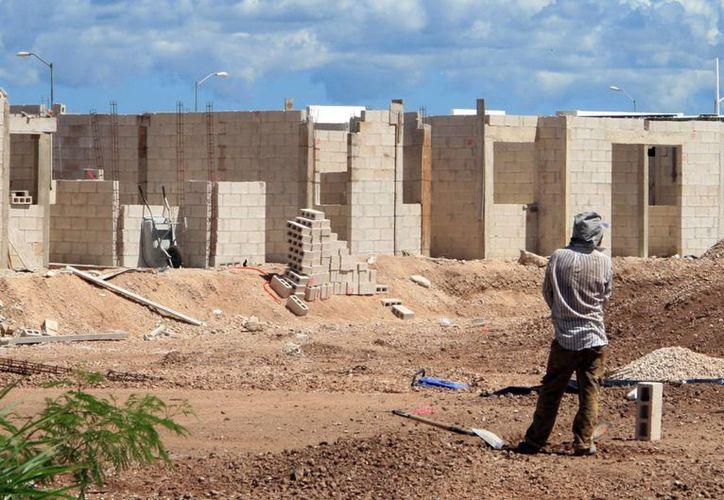 Este año el IVEY ejerció en acciones de vivienda casi 300 millones de pesos que beneficiaron a más de 15 mil familias en Yucatán. Foto de contexto de un hombre que mira la construcción de casas en un nuevo fraccionamiento. (Archivo/SIPSE)