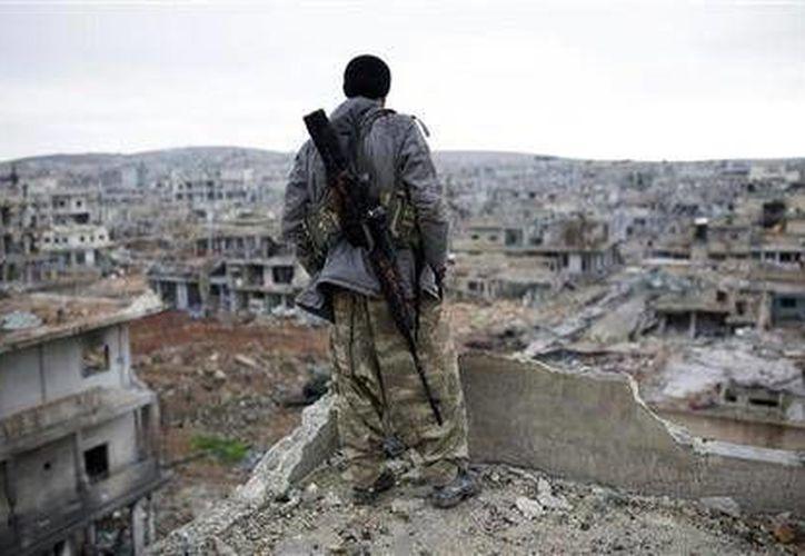 En fotografía, rebelde kurdo mira a los escombros de la ciudad siria de Ain al-Arab, en enero pasado. La tensión crece en el conflicto entre el gobierno de Turquía y rebeldes Kurdos tras el asesinato de dos policías turcos, la semana pasada. (Archivo AP)