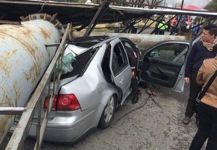 Debido a los fuertes vientos que se registraron ayer, un espectacular cayó sobre dos automóviles en Metepec. (twitter.com/Deb_Estrella)