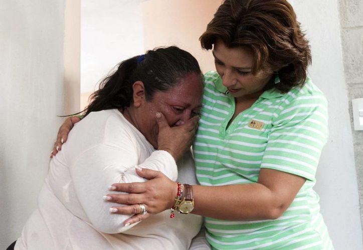 Genny Huchim Chan visiblemente conmovida tras recibir las llaves de su nueva casa. La acompaña la presidenta del DIF Yucatán, Sarita Blancarte de Zapata. (Cortesía)