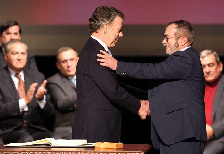 El presidente de Colombia Juan Manuel Santos (i) y el jefe máximo de las FARC Rodrigo Londoño Echeverry (d) se felicitan luego de firmar el nuevo acuerdo de paz. (EFE)