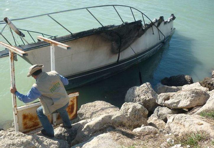 La Profepa levantó un acta por posibles delitos contra el medio ambiente, en el caso del barco que se incendió frente a la costa yucateca. En la imagen, un inspector verifica los restos de la embarcación. (Cortesía)