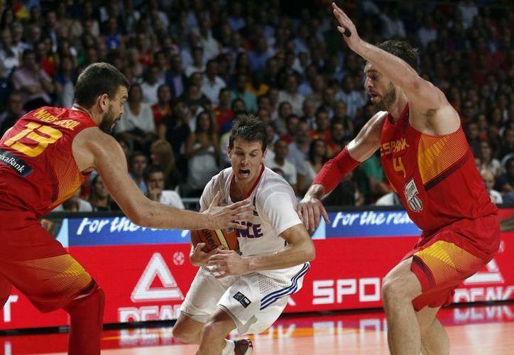 El francés Thomas Heurtel (c) avanza entre los españoles Marc y Pau Gasol (d), durante uno de los partidos de cuartos de final del Mundial de Basquetbol que se realiza en Madrid. (Foto: AP)