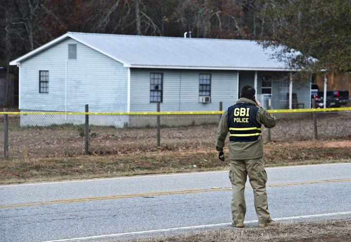 El agente especial del Buró de Investigaciones de Georgia J.T. Ricketson trabaja en la escena de un tiroteo en el que dos policías resultaron heridos al ejecutar una orden de allanamiento este lunes. El sospechoso murió en el lugar. (Woody Marshall/The Macon Telegraph via AP)