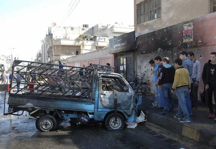 Los bombardeos ordenados por el régimen sirio no cesan. En esta foto se aprecia una congregación junto a un vehículo dañado por la caída de proyectiles en la plaza al-Haf Atef, en Homs, Siria. (Efe/Foto de contexto)