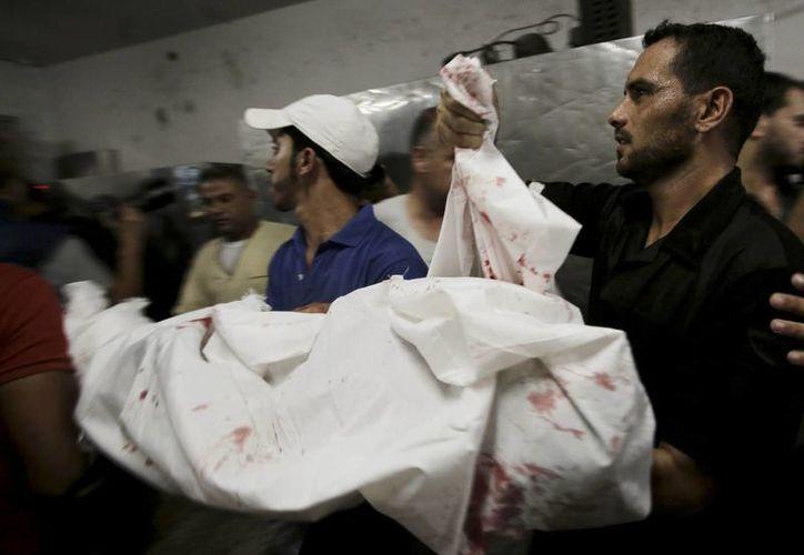 Hombres cargan los cadáveres de varios menores en el hospital de Gaza. Los niños fueron algunas de las víctimas de los más recientes ataques de Israel.  (Agencias)