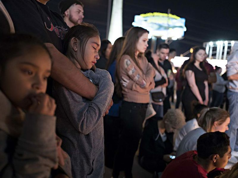 Attendees of a vigil for the victims of the latest school shooting in Texas, listen to speakers at the Arizona Capitol, in Phoenix.